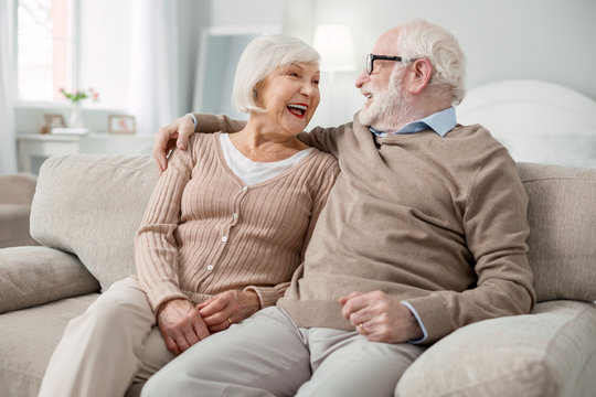 Happy together. Joyful elderly couple smiling to each other while being in a great mood
