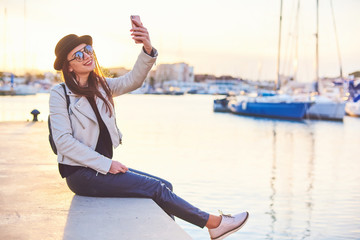 Pretty young woman in black hat sitting on a pier with a phone at a sea port