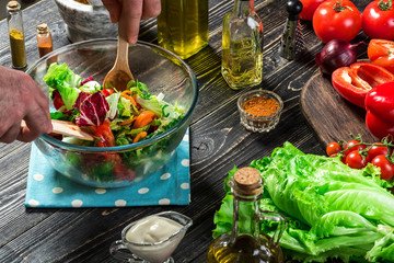 Man preparing salad with fresh vegetables on a wooden table. Cooking tasty and healthy food. Close-up
