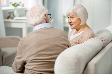 Pleasant conversation. Positive pleasant aged couple talking while sitting together in the sofa
