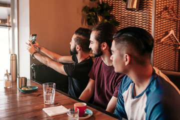 Group of arab friends taking selfie in lounge bar. Mixed race young men having fun. Best friends hangout together