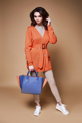 Portrait sexy beautiful woman pretty face bright makeup cosmetic face care long curly hair brunette wear clothes knitted wool jacket orange belt date or party catalog spring collection accessory bag.
