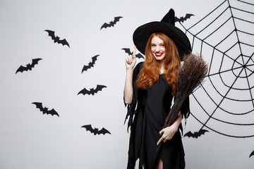 Halloween Concept - Happy elegant witch with broomstick halloween doing pointing finger on side.