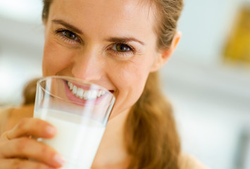 Smiling young woman drinking milk
