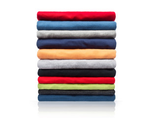 New colored clothing stacked in a pile close-up on white background