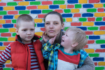Happy mother hugs her two charming sons, blond and shaten, against the backdrop of multicolored brick wall. Caucasian children and mom have good time together.
