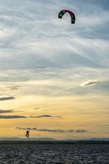 un kitesurfer en l'air pendant un saut et sous un coucher de soleil