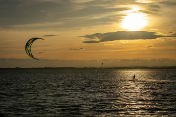 Un kitesurfer sous un coucher de soleil orange