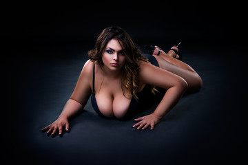 Plus size sexy fashion model in lingerie, fat woman with big natural breast on black studio background, overweight female body