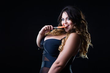 Plus size sexy model in lingerie licks lollipop, fat woman with big natural breast on black studio background