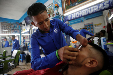 Barber Francisco Gomez who lost his hand three years ago in a fireworks accident, shaves the eyebrow of a man at 'Benedicion' barber shop in Tegucigalpa