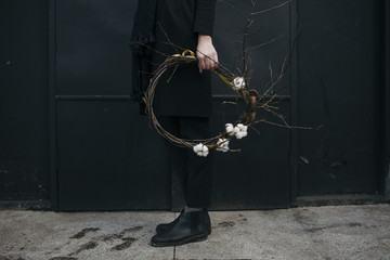 Low section of man holding cotton boll wreath outdoors