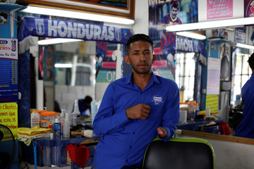 Barber Francisco Gomez, 25, who lost his hand three years ago in a fireworks accident, poses for a picture at 'Benedicion' barbershop in Tegucigalpa