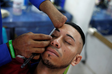 Barber Francisco Gomez, 25, who lost his hand three years ago in a fireworks accident, shaves the eyebrow of a man at 'Benedicion' barbershop in Tegucigalpa