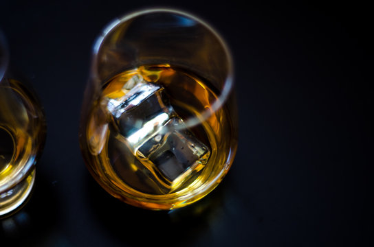 Scottish whisky in a glass with ice cubes, golden color whiskey