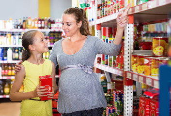 Woman with daughter are choosing fresh goods in food department