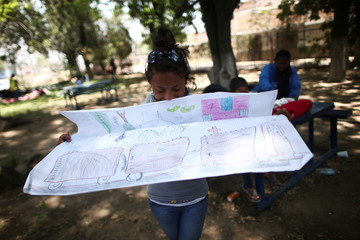 Katherine, 14, a Central American migrant from Guatemala, moving in a caravan through Mexico, shows her drawing at an improvised shelter, in Irapuato