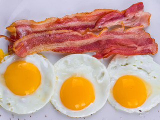 Fried egg with bacon on white plate. Delicious colorful English breakfast.