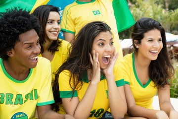 Laughing brazilian soccer fans with flag