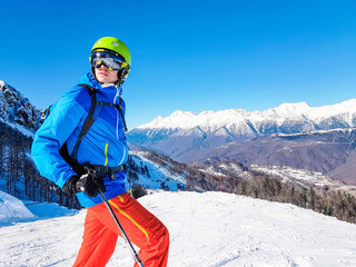 Photo of skier wearing helmet against background of mountains and blue sky
