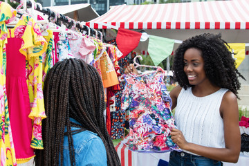 African american woman presenting colorful clothes at market