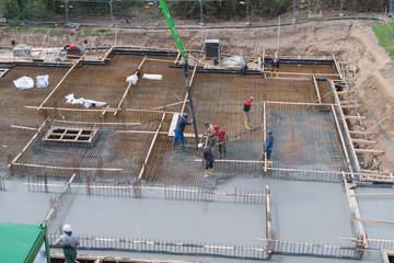 Flüssigbeton wird in Eisen des Fundaments eines Gebäudes eingefüllt