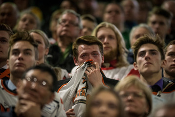 An attendee sheds tears at a memorial for Evan Thomas, one of the players killed in the bus crash carrying the Humboldt Broncos Junior A hockey team