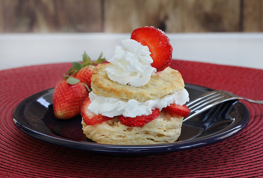 Fresh strawberry shortcake with homemade biscuits and garnished with a sliced strawberry.