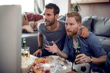 Friends enjoying soccer on TV