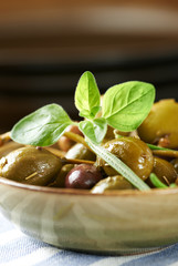 Different marinated olives and capers in a small ceramic bowl. Vertical.