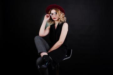 Studio portrait of blonde girl in black wear, red hat and glasses against dark background.