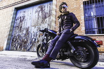 Modern biker sits on classic motorcycle looking at his back and checking the industrial bricks buildings. Outdoor portrait and urban lifestyle