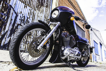 Close-up custom motor bike holds on a vintage industrial street. Outdoor portrait and urban lifestyle