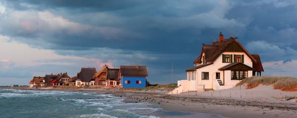 Fototapete - Strandvillen auf der Halbinsel Graswarder in Heiligenhafen in Schleswig-Holstein an der Ostsee bei Sonnenuntergang im letzten Sonnenlicht