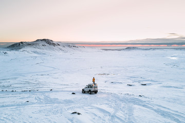 Male in yellow jacket standing on a jeep on top of Eyjafjallajökull glacier in Iceland during sunset