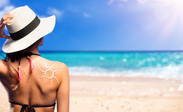 Girl With Suntan Lotion Shaped Sun In The Beach
