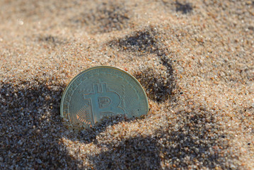 Physical golden bitcoin coin on sand