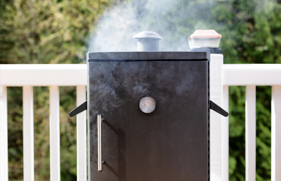 Close up of a smoker with fresh smoke coming out of barbeque cooker