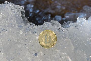 Physical golden bitcoin coin on ice