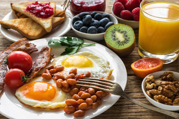 English breakfast served with fried egg, beans, tomatoes, orange juice, bacon and toast with fresh fruits and berries
