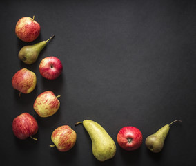on a dark black background red yellow green apples pear frame top view flat lay