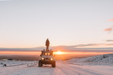 Adult male standing on top of heavy duty vehicle on Eyjafjallajökull glacier in Iceland in winter during sunset