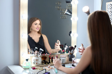 Young woman with makeup made by professional artist applying perfume in dressing room