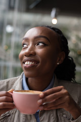 Smiling woman holding a coffee cup and looking away