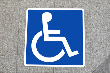 Symbol of a wheelchair on ground of the sky train station indicates a wheelchair area.
