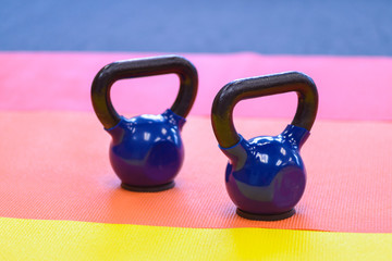 a set of two blue kettle bells sitting on colourful exercise mats. horizontal and room for copy