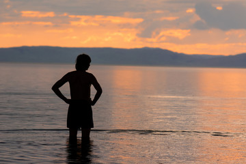 silhouette of a man who stands in the water and looks towards the sunset