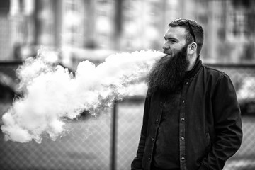 Vape bearded man in real life. Portrait of young guy with large beard in glasses vaping an electronic cigarette opposite urban background in the spring. Black and white.