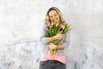 Young pretty woman with a bouquet of flowers stands in front of concrete wall and is happy about mother's day, birthday, wedding day