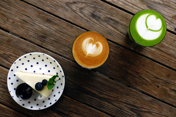 A cup of green tea matcha latte and cup of latte art coffee on wooden background